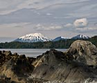 The shoreline rocks accentuate the shape of the mountains across the bay from Sitka.