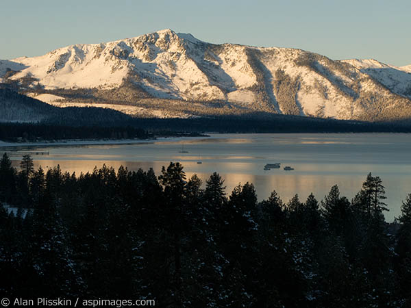 Late afternoon Winter light illuminates the mountains surrounding Lake Tahoe.