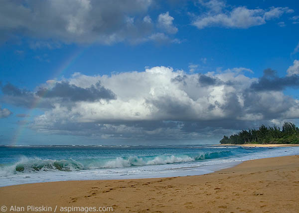 Rainbow over the breaking surf at Anini Beach in Kauai.