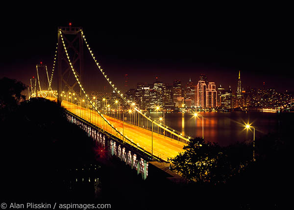 The lights of San Francisco glow across the Bay beyond the Oakland Bay Bridge.