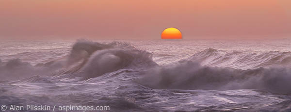 The sun sets in the Pacific Ocean past the wavebreaks at Ke'e Beach.