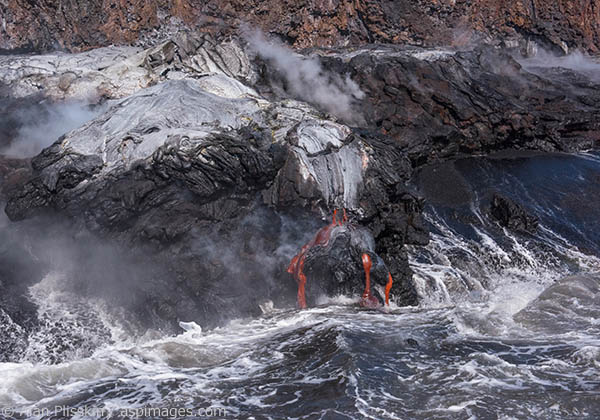 The lower land formed the previous week was created by the lava flow in the image with the boat.  The eruption of Mauna Loa over the past 3 decades has added hundreds of acres of land to the Big Island, Hawaii.