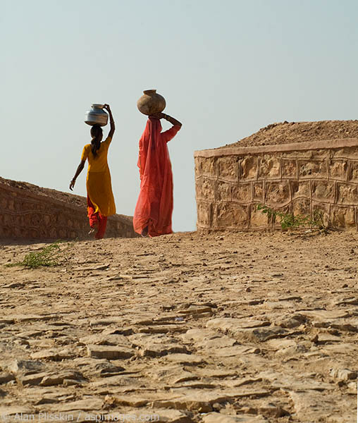 Two women carrying water home, a daily household chore.