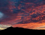Mt Tamalpias is silhouetted against a colorful evening sky.