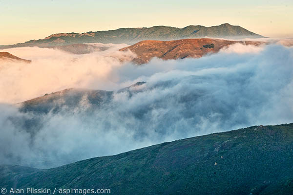 Early morning fog breaks up as the sun lights Mt Tamalpais and other ridges in the Marin Headlands.