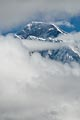 The summit of Everest shows through the breaking clouds.