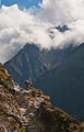 A distant mountain breaks through the clouds as this hiker reaches a crest in the trail.