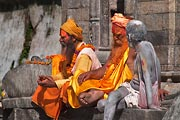 Three Hindu Sadhus are having a serious discussion at a Kathmandu monument.
