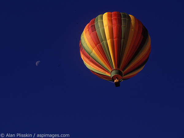 The moon behind a hot air balloon during the Park City balloon festival.