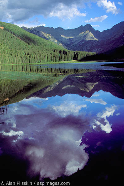Cumulus cloud reflects in this Rocky Mountain lake near Vail, Colorado.